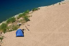 Lonely tent on the beach 2. Alone standing blue tent placed on the edge of the sandy beach and blue waters of the river Stock Photography