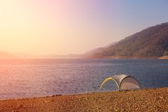 Lonely tent on mountain lake shore. Lonely tent on mountain lake shore at sunrise - tranquil meditation scene Stock Photo