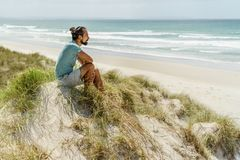 Lonely thoughtful man sitting on seashore and looking at sea Rarawa beach. New Zealand royalty free stock photos