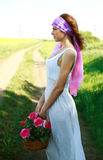 Lonely thoughtfully girl with basket flowers in a field Stock Photo