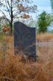 Lonely tombstone granite slab near the road. Royalty Free Stock Photos