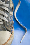 Lonely torn sneakers. Old leaky sneakers on a blue background Stock Photos