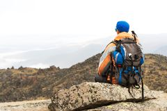 A lonely tourist with a backpack and in sunglasses is resting sitting on a rock. A lonely tourist with a backpack and sticks for movement in the mountains. In Royalty Free Stock Photography
