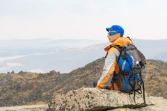 A lonely tourist with a backpack and in sunglasses is resting sitting on a rock. A lonely tourist with a backpack and sticks for movement in the mountains. In Royalty Free Stock Images