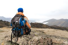 A lonely tourist with a backpack and in sunglasses is resting sitting on a rock. A lonely tourist with a backpack and sticks for movement in the mountains. In Stock Images