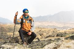 A lonely tourist with a backpack and in sunglasses is resting sitting on a rock. A lonely tourist with a backpack and sticks for movement in the mountains. In Stock Photos