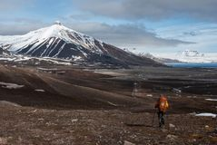 Lonely tourist hiking towards snow capped mountain in the Russian ghost town Pyramiden in Svalbard archipelago. In the high Arctic Stock Photography