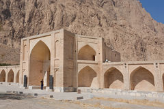 Lonely tourist standing at entrance of stone caravanserai structure, ancient hotel in Iran Stock Photo