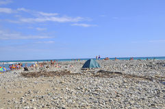 Lonely tourist tent on the coast among the many vacationers Royalty Free Stock Images