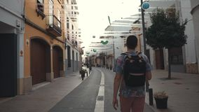 Lonely tourist is walking on ancient streets in small picturesque city in summer stock footage