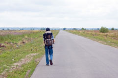 The lonely tourist walks afar the road Royalty Free Stock Photos
