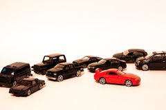 Unique toy car. The red one toy car with a lot of black cars isolated on the white background Stock Photos