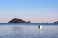 Lonely traditional greek fishing boat on sea water Stock Photo