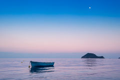 Lonely traditional greek fishing boat on sea water Stock Images