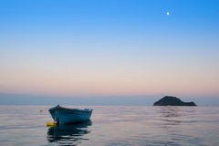 Lonely traditional greek fishing boat on sea water Stock Photos