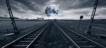 Lonely train track and a surreal full moon Stock Photography
