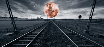 Lonely train track and a surreal full moon Stock Images