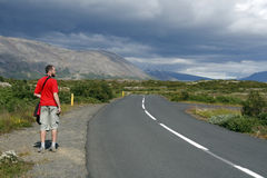 Lonely traveller. Hitchhiking along the road in beautiful mountainous region of Iceland Royalty Free Stock Image