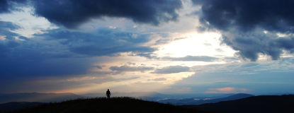 Lonely traveller across the mountains Royalty Free Stock Photo