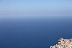 Lonely traveller on the cliff edge Royalty Free Stock Image