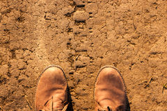 Lonely traveller. 's boots on a muddy road royalty free stock photos