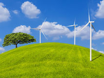 Lonely tree and wind turbines on green field with blue sky Stock Photos