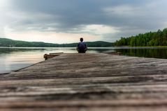 A lonely trekker on a jetty on the Saimaa lake in the Kolovesi N. Ational Park in Finland at sunset - 2 stock photos