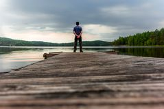 A lonely trekker on a jetty on the Saimaa lake in the Kolovesi N. Ational Park in Finland at sunset - 1 stock images