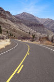 Lonely Two Lane Divided Highway Cuts Through Dry Mountainous Lan Stock Photo