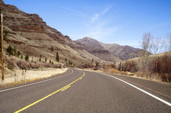 Lonely Two Lane Divided Highway Cuts Through Dry Mountainous Lan Royalty Free Stock Photos