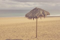 Lonely umbrella on the beach. Vintage parasol, retro photo. Stock Image