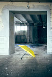Lonely umbrella. A yellow umbrella in an old factory Stock Photography