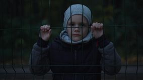 Lonely unhappy, miserable young boy behind and clinging to fence