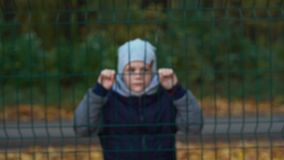 Lonely unhappy, miserable young boy behind and clinging to fence - slow motion