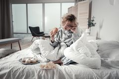 Lonely unhappy woman eating and crying after breakup. Eating and crying. Lonely unhappy woman eating and crying after breakup while sitting in her bedroom stock images