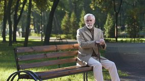 Lonely upset old man sitting alone in park and thinking about life, pensioner