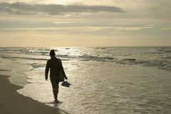 Lonely walk. Walking by the sea in sunset light Stock Image