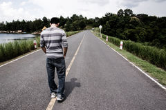 Lonely walk. A guy stands in front of a long lonely road Stock Image
