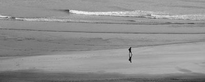 The lonely walk. Lonely man walking by the ocean Stock Images