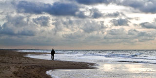 Lonely walk. A man alone with his thoughts walks along the North Sea's floodline Royalty Free Stock Image
