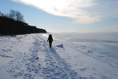 Lonely walk. Woman walks lonely along a beach in a winter landscape Stock Photo