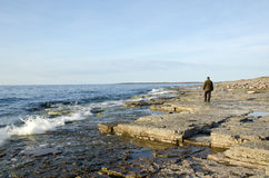 Lonely walk. A man walks alone along a coast Stock Images