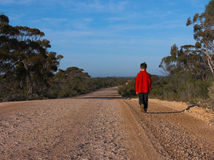 Lonely walk. Boy walking on a lonely country road Royalty Free Stock Photos