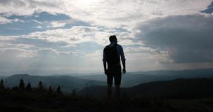 Lonely walk in the mountains. Look from behind at a man with backpack standing before beautiful mountain landscape and stock video