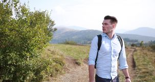 Lonely walk in the mountains. Man walks along the road on a hill with great landscape before him and looks over his stock video