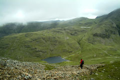Lonely walker descending from Great Gable to Styhead Tarn Stock Photo