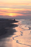 Lonely walker in evening sunlight, Ameland, Holland stock photos