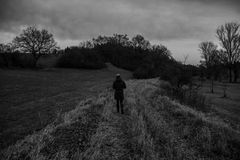 Lonely wanderer. Person walking alone in moody rural black and white landscape Royalty Free Stock Image