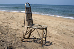 The lonely wattled chair costs on a beach, against the sea. GOA India beach Royalty Free Stock Image