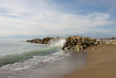Lonely wave breaks against mass of stones. A Mediterranean seascape with waves, stones, rocks, sand and wet seashore in a daylight royalty free stock images